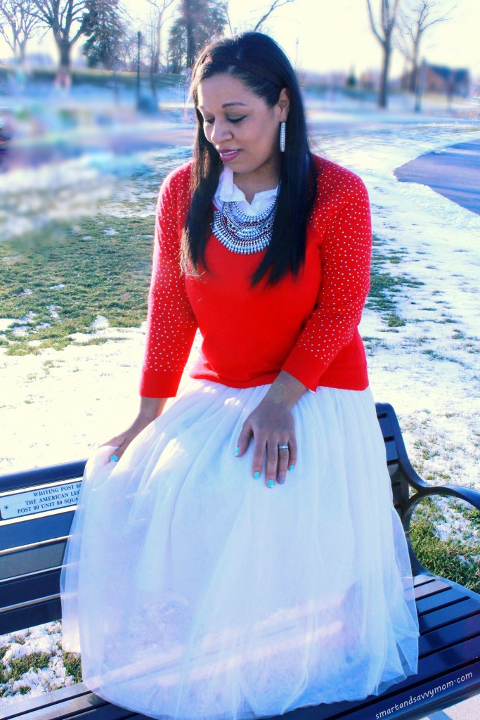red embellished sweater with statement necklace and tulle skirt winter outfit on bench