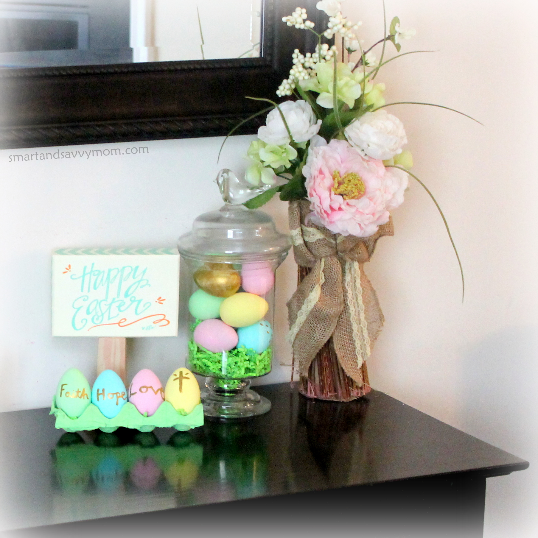 Console table Easter decor with hand painted eggs, happy easter sign, and kirkland's pink flower arrangement