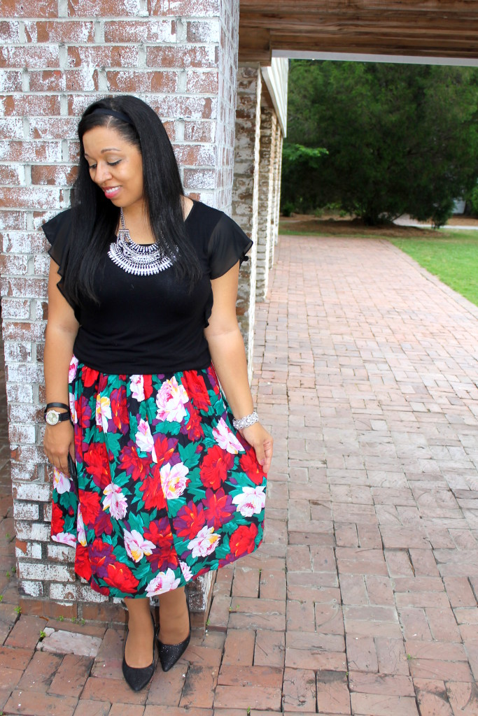 modern style with vintage pieces. Red, pink, green and black floral skirt with black top and statement necklace. Modest fashion